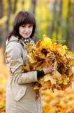有秋叶的美丽的少妇 库存图片