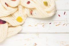 有秋叶的被编织的温暖的衣裳在一张木桌上的一个秋季设置 舒适,温暖,舒适 免版税库存照片