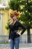 有秋叶花圈的美丽的金发碧眼的女人  免版税库存图片