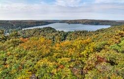 有秋天五颜六色的结构树的湖在前景 库存照片