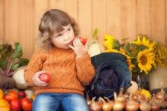有秋天收获的可爱的微笑的小孩女孩 免版税库存图片
