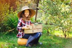 有秋天收获的愉快的农夫儿童女孩-有机南瓜、红萝卜和夏南瓜从自己的庭院采摘了 免版税库存照片