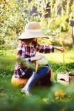 有秋天收获的愉快的农夫儿童女孩-有机南瓜、红萝卜和夏南瓜从自己的庭院采摘了 免版税图库摄影