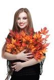 有秋天槭树叶子的微笑的少妇 免版税库存图片