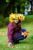 有秋天槭树的愉快的少妇在公园把诗歌选留在。 免版税库存照片