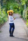 有秋天槭树的愉快的少妇在公园把诗歌选留在。 免版税图库摄影