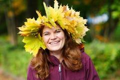 有秋天槭树的愉快的少妇在公园把诗歌选留在 免版税库存照片