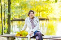 有秋天槭树的愉快的少妇在公园把诗歌选留在 免版税库存图片