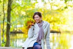 有秋天槭树的愉快的少妇在公园把诗歌选留在 免版税图库摄影