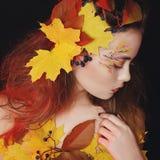 有秋天的美丽的少妇在演播室做摆在  免版税库存图片
