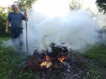 有秋天篝火的年长人 库存照片