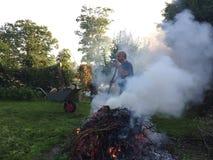 有秋天篝火的年长人 图库摄影