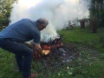 有秋天篝火的年长人 免版税图库摄影