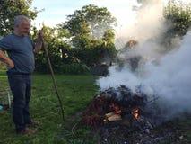 有秋天篝火的年长人 免版税库存照片