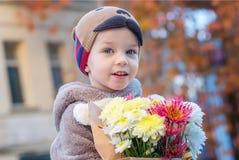 有秋天花束的一个小男孩在背景 库存图片