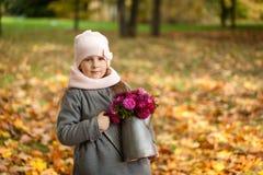 有秋天花束的女孩在一个喷壶 库存图片