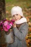 有秋天花束的女孩在一个喷壶 免版税库存照片