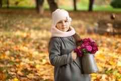 有秋天花束的女孩在一个喷壶 图库摄影