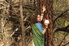 有种族构成的女孩和一个小手鼓在森林里 免版税库存照片