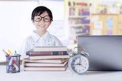 有科学书和膝上型计算机的女孩在类 免版税库存图片