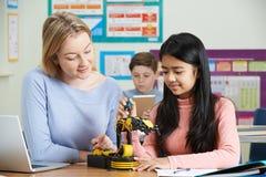 有科学教训的学习机器人学的女性学生的老师 库存照片