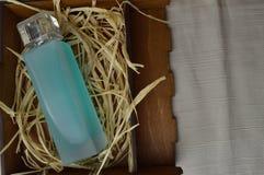 有科隆香水的,润肤水,在一个木自创箱子的香水蓝色,美丽,玻璃瓶有干秸杆的 免版税库存照片