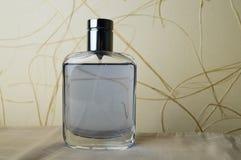 有科隆香水的,润肤水,在米黄墙纸背景的香水蓝色,美丽,玻璃瓶  库存图片