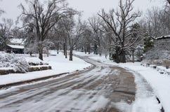 有积雪的房子和树的冰冷的城市邻里街道 库存照片