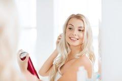 有称呼她的头发的喷发剂的妇女在卫生间 免版税库存照片