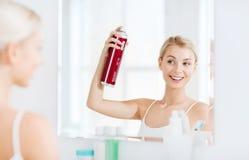 有称呼她的头发的喷发剂的妇女在卫生间 库存图片