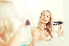 有称呼的做她的头发的铁妇女在卫生间 图库摄影