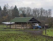 有秸杆大包的蓝色拖拉机在门廊和种田下用工具加工树 库存图片