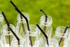有秸杆的小玻璃瓶为coctails做准备在党 免版税库存图片