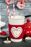 有秸杆的杯在红色被编织的取暖器 库存照片