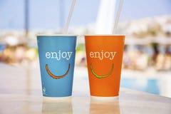 有秸杆的蓝色和橙色纸咖啡杯和享受标志 图库摄影