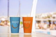 有秸杆的蓝色和橙色纸咖啡杯和享受标志 免版税库存图片