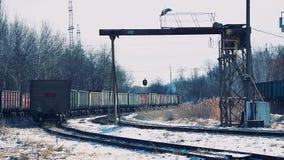 有移动沿积雪的火车站的运货车的柴油火车