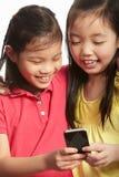 有移动电话的二个中国女孩 免版税库存图片