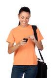 有移动电话的俏丽的学员女孩 库存照片