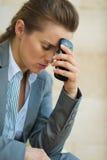 有移动电话的关心的女商人 库存照片
