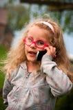有移动电话的小女孩 库存照片