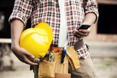 有移动电话的建筑工人 库存图片