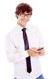 有移动电话的微笑的少年在他的现有量 库存图片
