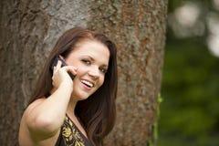 有移动电话的微笑的美丽的深色的妇女 库存照片