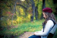 有移动电话的秋天女孩 库存图片