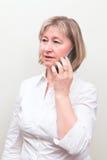 有移动电话的美丽的中年白肤金发的妇女 库存图片