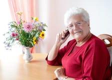 有移动电话的老妇人 免版税库存照片