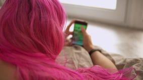 有移动社会媒介的桃红色头发的女孩 股票录像