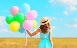 有空气五颜六色的气球的后面看法妇女在草帽享受在领域和蓝天的一个夏日 免版税库存照片