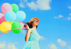 有空气五颜六色的气球的愉快的年轻微笑的妇女获得穿在蓝天背景的乐趣一个夏天草帽 库存照片